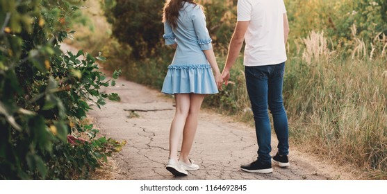 Young loving couple standing back and holding hands, love, lifestyle
