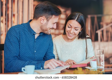 Young loving couple, students, sitting in a cafe while learning together and preparing for the seminar. Education, relationships, love concept