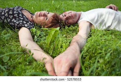 Young loving couple teenagers sitting on green grass. Two Caucasian people