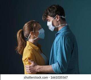 Junger liebender Ehepaar, der Gesichtsmasken trägt, die Augen des anderen umarmt und starrt, Vorsorge gegen Virusverbreitung und Gefühle-Konzept