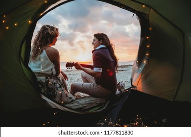 Young loving couple while camping on the seashore a summer evening at sunset. A woman plays the guitar. View from the tent