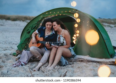 Young loving couple while camping on the seashore a summer evening at sunset. One woman plays the guitar while the other is listening to her