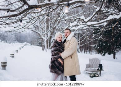 Young loving fashionable beautiful wedding emotional couple outdoor in winter in a stylish fur coat. Beauty, happiness, love, seasons concept