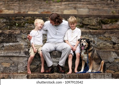 A young, loving father is sitting outside on stone steps, with his two boy children and their adopted pet German Shepherd dog on a Summer day.