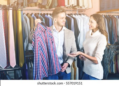 4f164a65 Young loving happy couple deciding on new shirt in menâ??s cloths store.  Happy young male with new clothes ...