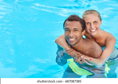 Young loving mixed race couple - black guy and caucasian girl hugging standing in swimming pool during holiday on warm summer day