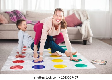 Young loving mother having fun with her child indoors. Pretty mom and her little son playing twister at home.