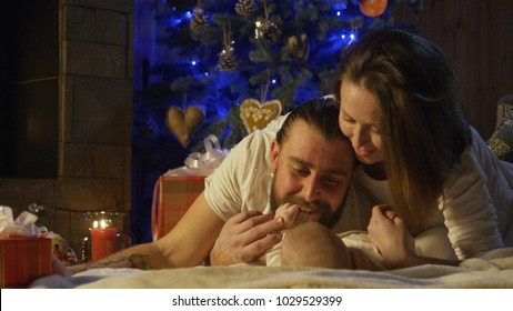 Young loving parents playing with their newborn baby in front of a decorated Christmas tree with lights at night spending time together.
