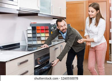 Young loving smiling cheerful positive couple choosing household appliances for their kitchen in store