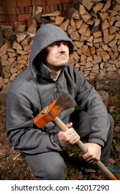 Young lumberjack splitting wood with an axe