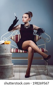 Young luxurious rich girl in black dress sitting on a sofa holding cigarette holder with cigarette in hand with long gloves and jewelry