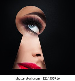 young luxurious woman looks at something secret in the keyhole. The concept of secret of beauty, new cosmetics. Eye makeup close - up, copy space to the right ,