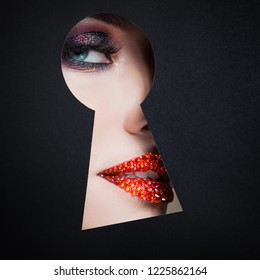 young luxurious woman looks at something secret in the keyhole. The concept of secret of beauty, new cosmetics. Eye makeup close - up,