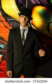 Young ma in top hat and cane against abstract background