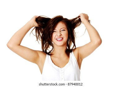 Young mad caucasian girl pulling her hair. Isolated on white.