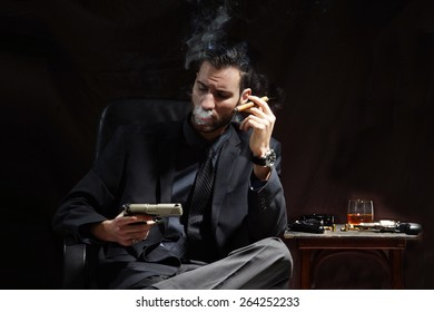 Young mafia man hold gun and smoke cigar on dark background