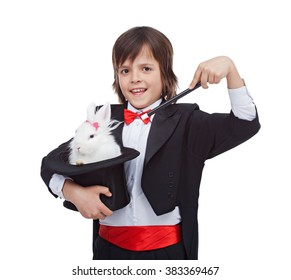 Young magician boy smiling, holding cute rabbit in his magic hat - isolated