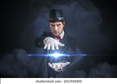 Young magician man is showing bright ball that levitates. Black background.