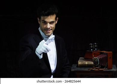 Young magician  with old vintages cameras on dark background