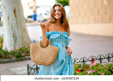 Young magnificent feminine smiling woman, wearing elegant blue dress and straw bag, walking on the city center at beautiful sunny spring summer day.