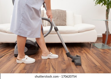 Young Maid Cleaning Floor With Handheld Vacuum Cleaner