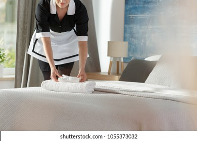 Young maid laying fresh towels on a bed in a hotel room