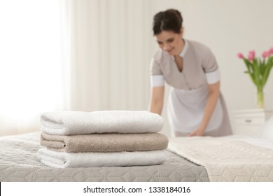 Young maid making bed in hotel room, focus on stack of towels
