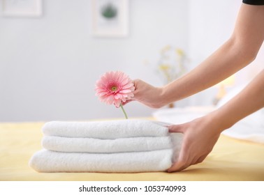 Young maid putting flower on stack of towels in hotel room