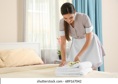 Young maid putting flowers on stack of towels in hotel room