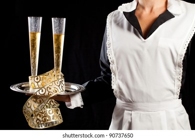 Young maid in uniform serving two glasses of champagne with tray and festive gold decorations