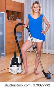 Young maid using modern hoover during clean-up indoors