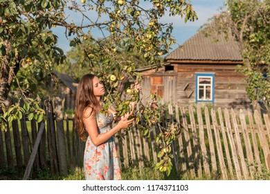 a young maiden woman stands near the garden fence in front of an old village house and closes her eyes in the rays of the morning sun