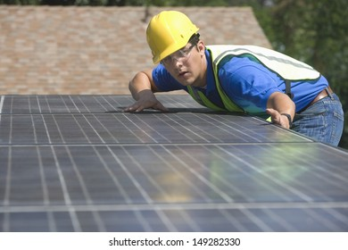 Young maintenance worker installing solar panels on rooftop