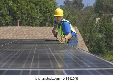 Young maintenance worker measuring solar panels on rooftop