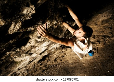 Young make climber doing a rock wall on a cave.