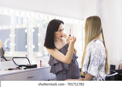 Young makeup artist doing makeover to pretty model at beauty salon