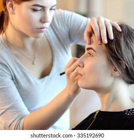 young makeup master looking at woman`s makeup in salon