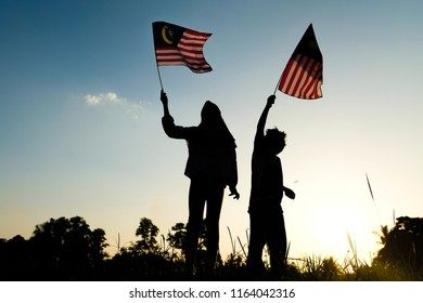 A young malay boy and a girl with hijab smiling while waving a Malaysian flag outdoor during sunset