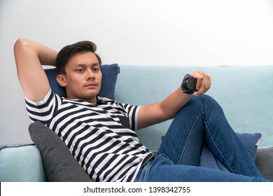 Young Malay man at the Sofa watching tv relaxing