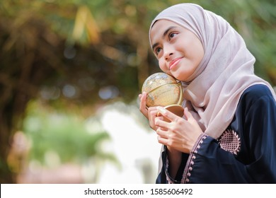 Young Malay muslim student girl in hijab black clothes hold in hands Earth world globe  with blurry background.  People religious lifestyle concept. Mock up copy space