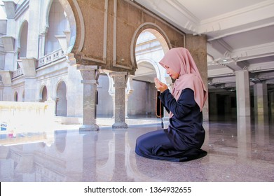Young malay muslim woman hold her hands up while praying in a mosque.