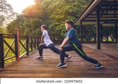 young Malaysian teen Athletic warming up and stretching before morning fitness running training workout in outdoor park with sunrise in background. concept of healthy living in nature