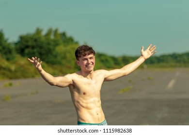 Young male adult with his arms out enjoying the sunshine shirtless on a warm summer's day
