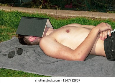 Young male adult laying in the sun sleeping under a book