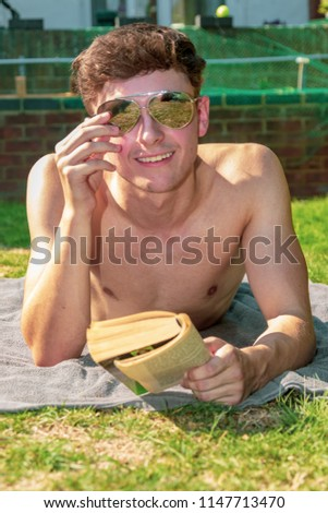 Young male adult laying in the sun reading a book