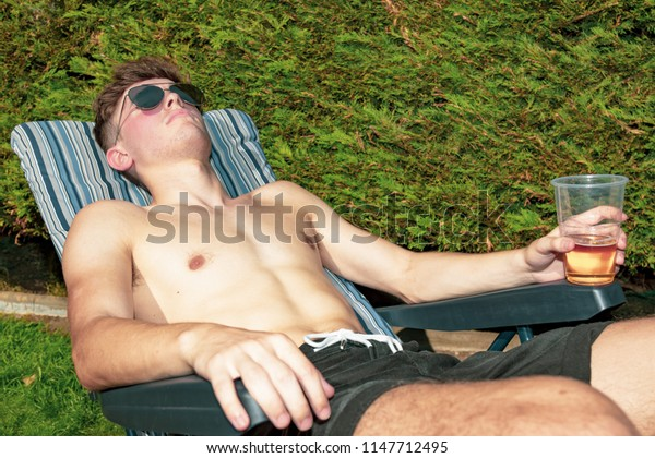 Young male adult laying in the sun with a beer