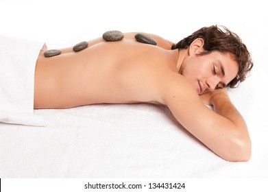 young male adult receiving a hot stone massage laying down. studio shot isolated on white.