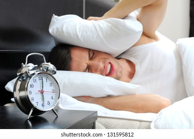 Young male adult stressed by his alarm clock with his head under the pillow in the bedroom