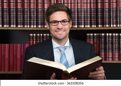 Young male advocate reading legal book at courtroom