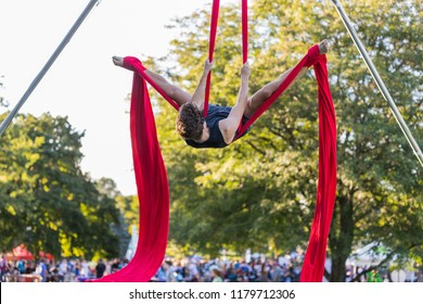 Young male aerial acrobatic dancer is is doing a split on a red ribbon